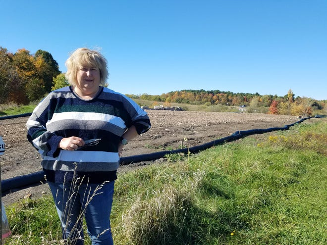 Julie Randolph stands near the construction and demolition debris from Dover High School that was dumped on her neighbor's property and her own.