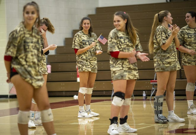 Big Walnut volleyball player Andie Stewart (in back) tries to hold back tears as her father, U.S. Army Lt. Col. Jon Stewart, enters the gymnasium prior to the match.