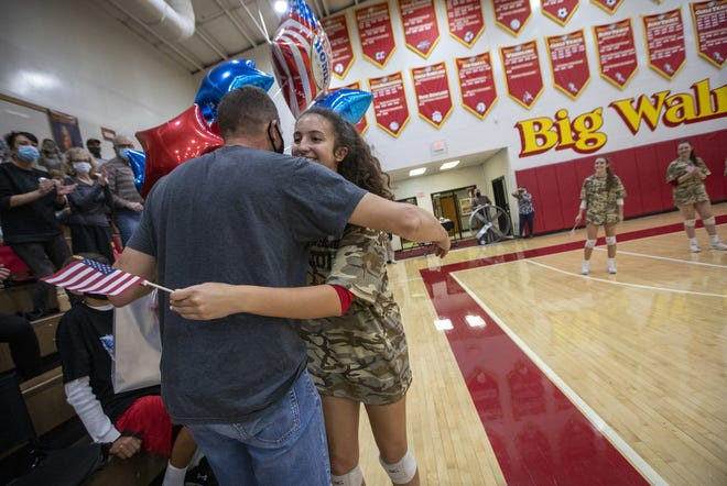 Dressed in military camouflage for warm-ups with all her teammates, Big Walnut High School girls volleyball player Andie Stewart welcomes home her father, U.S. Army Lt. Col. Jon Stewart, with a hug and balloons prior to the team's match against visiting Dublin Scioto on Oct. 13. Stewart was watching his daughter play for the first time in two seasons since being deployed to Kuwait, United Arab Emirates, Iraq and Saudia Arabia.