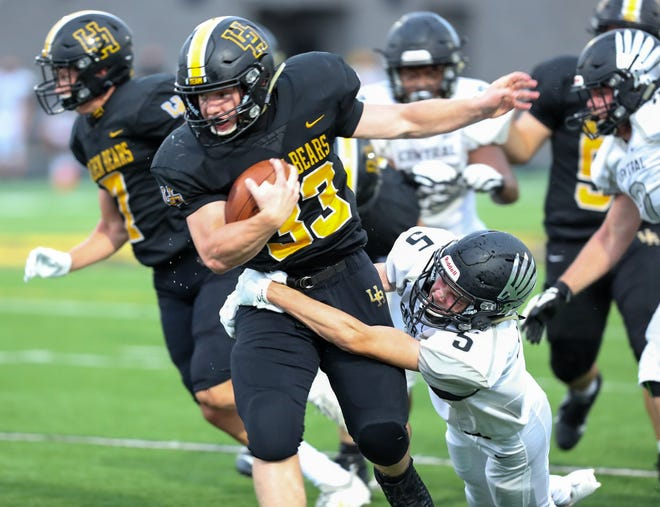 Upper Arlington's Carson Gresock tries to escape from the grasp of Westerville Central's Kyle Denney during the Warhawks' 28-23 win Aug. 28. The teams will meet again Friday, Oct. 16, in the Division I, Region 3 playoffs.