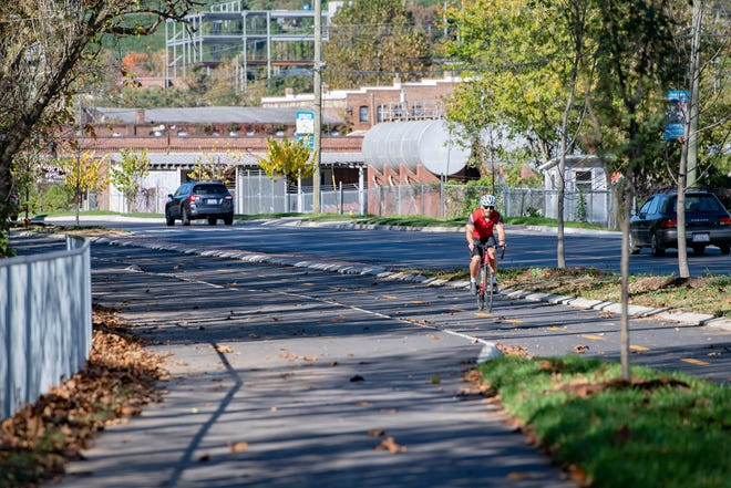 A bicyclist uses the divided bicycle lane along Lyman Street on the new French Broad River East Bank Corridor section of greenway in the River Arts District on Oct. 13, 2020. The greenway is part of the larger River Arts District Transportation Improvement Project, or RADTIP.
