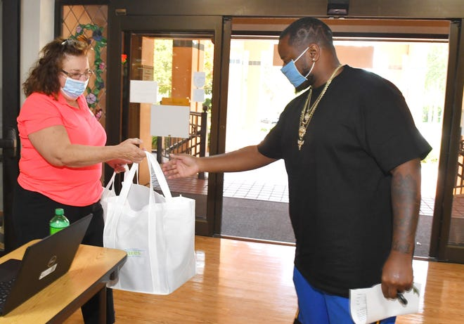Brevard County employee Leslie Rothering gives two personal protective equipment kits to Omar Fulton as part of a distribution to representatives of small businesses and restaurants who applied in advance for kits, which were funded through the Coronavirus Aid, Relief and Economic Security Act. The distribution on Tuesday was held at the Catherine Schweinsberg Rood Central Library in Cocoa.