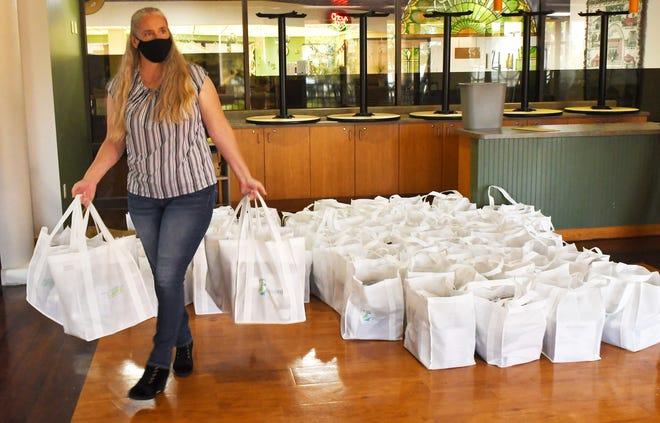 Brevard County employee Becky Tiegs gathers up personal protective equipment kits for small businesses and restaurants that applied in advance for county-provided kits during a distribution Tuesday at the Catherine Schweinsberg Rood Central Library in Cocoa.