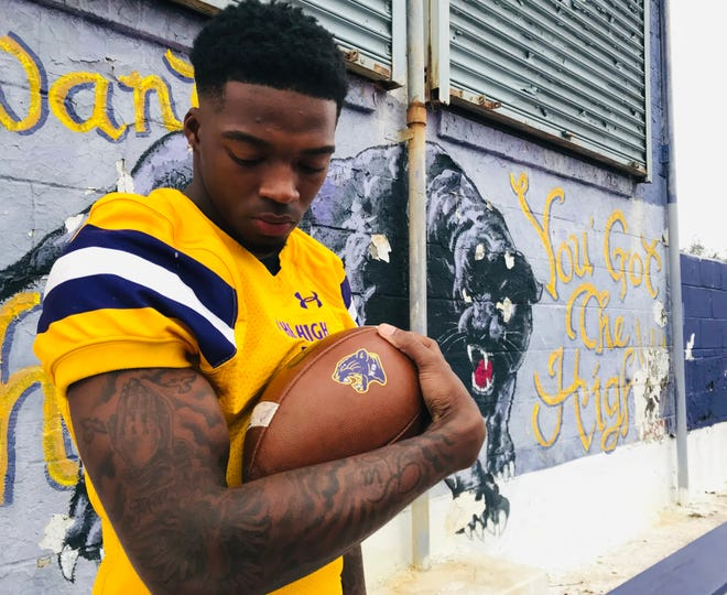Camden senior Alijah Clark holds a football next to a tattoo he got earlier this year in honor of his grandmother, Marilyn Clark, who passed away from COVID. Clark lost several family members and friends during the spring.