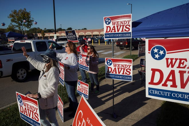 Wendy Davis and campaigners wave to passersby arriving to cast their vote on the first day at Montgomery County Election Commission in Clarksville, Tenn., on Wednesday, Oct. 14, 2020.
