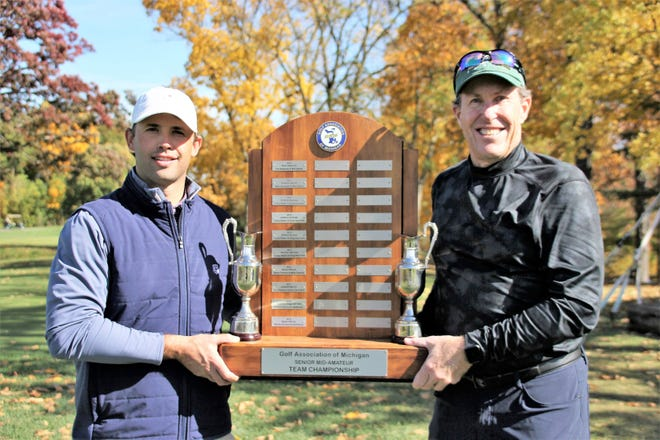 Scott Strickland, left, and Tom Gieselman hold the championship plaque after winning the Golf Association of Michigan Senior Mid-Amateur Team Championship Tuesday.