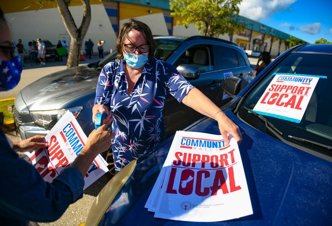 Kim Anderson Young distributes placard signs to place on vehicles preparing to participate in the Guam Chamber of Commerce's CommUNITY Rally  in this Oct. 14 file photo. She was elected to the 2021ChamberBoard.
