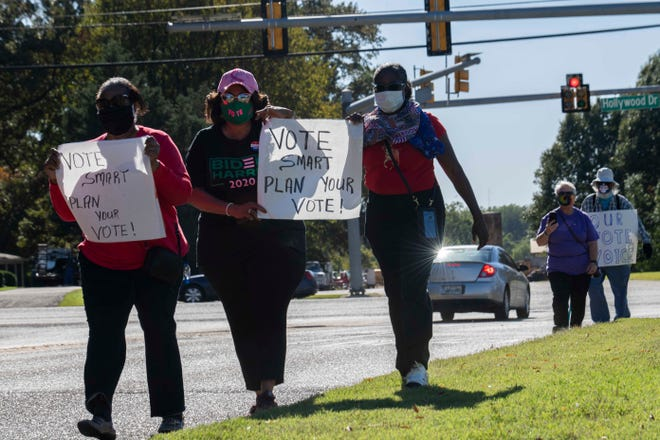 Marva Humphrey, Jennette Yander, and Deanea Mercer marches down a mile on North Parkway to Madison County Election Commission office to vote on the first day of early voting in Jackson, Tenn., Wednesday, Oct. 14, 2020.