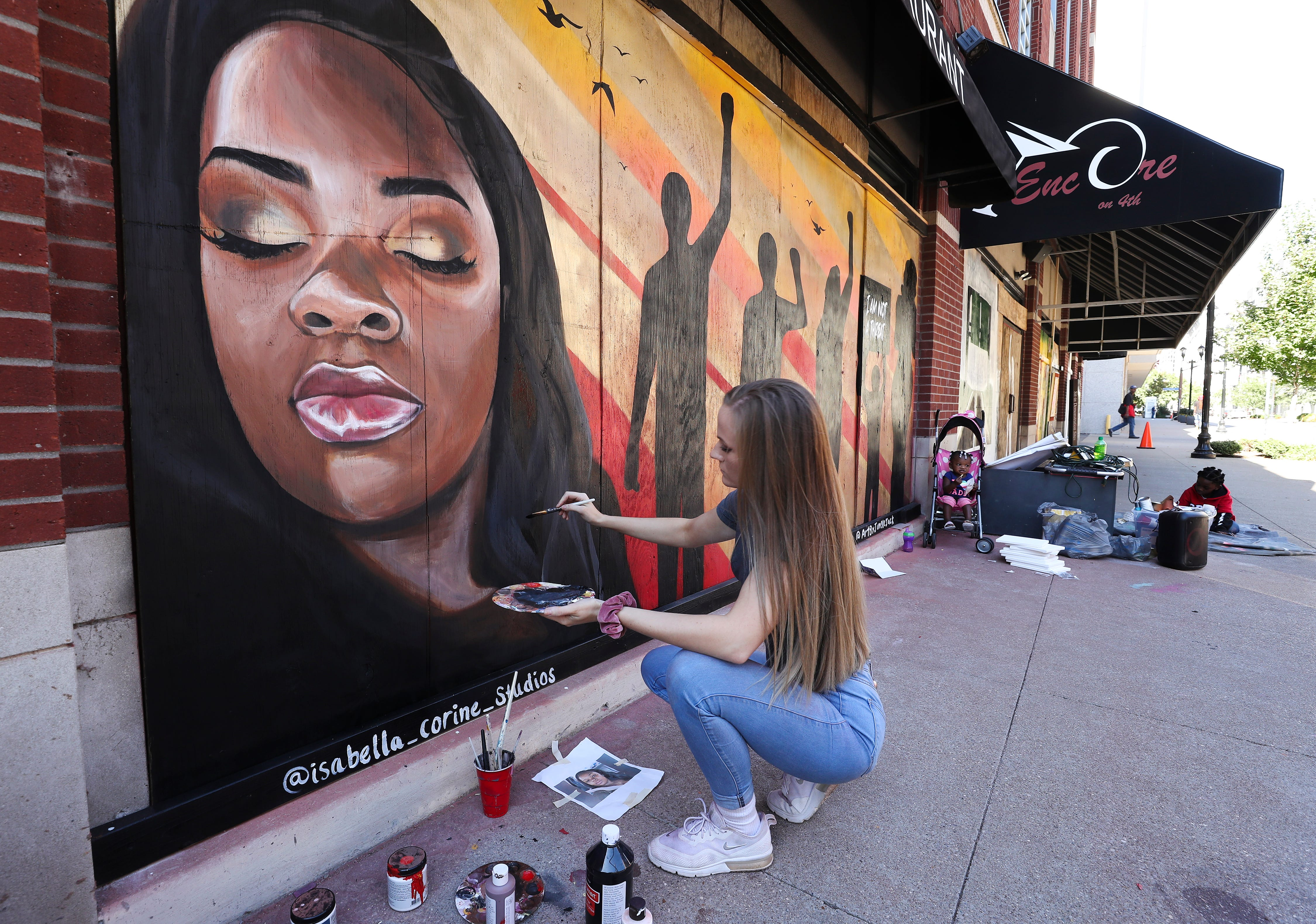 Isabella Siebert paints highlights on a mural of Breonna Taylor on boards covering the windows at Encore on S. 4th Street in Louisville, Ky. on Oct. 13, 2020.  Artists have been transforming the boards into art to be auctioned off and removed from downtown businesses.