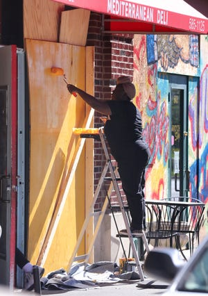 Tasha Grimes paints the background color before creating art on boards covering the windows at Safier on S. 4th Street in Louisville, Ky. on Oct. 13, 2020.  Artists have been transforming the boards into art to be auctioned off and removed from downtown businesses.