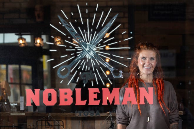 "Nikki Schneider, co-owner of The Nobleman, stands inside the barbershop Wednesday in Wauwatosa. Despite the possibility of vandalism during unrest last west, Schneider decided not to board up the windows or doors of her business at 6831 W. North Ave. ""We felt that boarding up sent a message that we don't want to hear from the people,"" Schneider said. ""So we just wanted to leave our windows open and not spread what we felt was fear that was spreading through the city."""
