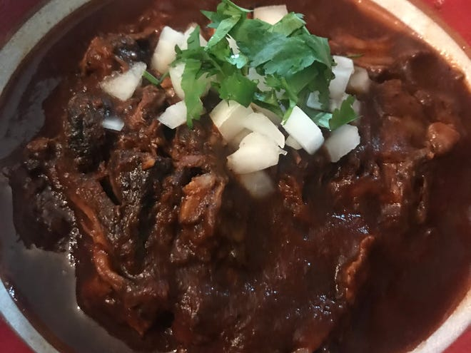 Garnish birria with chopped white onion and cilantro before eating.