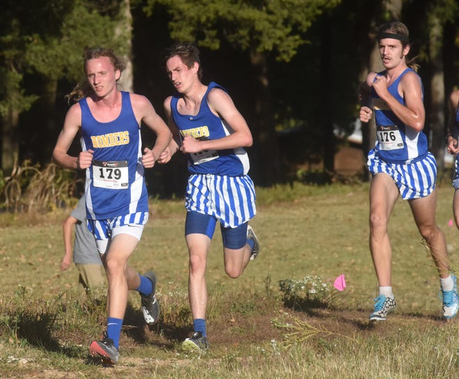 Mountain Home's Hendrix Hughes, Ky Bickford and Tyler Firment compete on the back half of Tuesday's Bomber Invitational cross country meet.