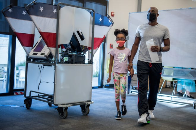 Paul Richardson walks with daughter, Kai, 8, after filling out his ballot during the first day of early voting at Casa Azafrán Community Center in Nashville, Tenn., Wednesday, Oct. 14, 2020.