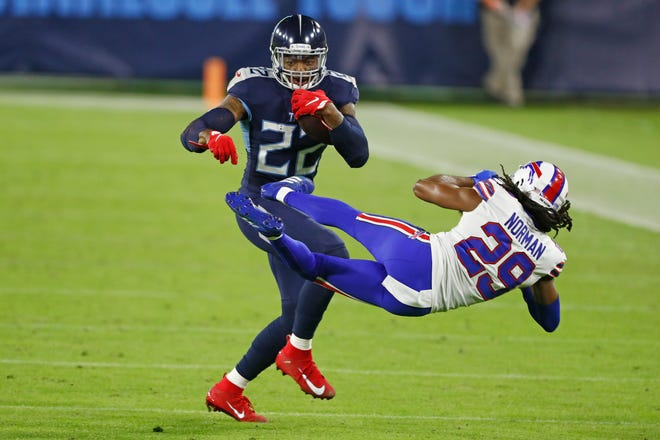 Tennessee Titans running back Derrick Henry (22) knocks down Buffalo Bills cornerback Josh Norman (29) in the first half of an NFL football game Tuesday, Oct. 13, 2020, in Nashville, Tenn. (AP Photo/Wade Payne)