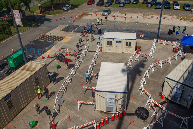 Local residents wait in line to get tested for COVID-19 at Bragg Memorial Stadium, Wednesday, Oct. 14, 2020.