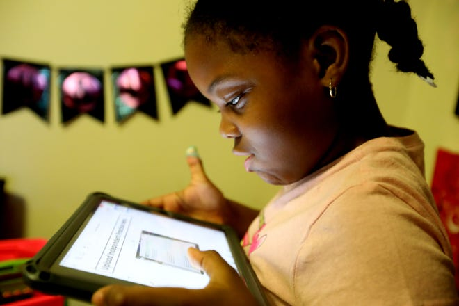 Khloe Johnson, 6, a second-grader at the Mamaroneck Ave. School in White Plains, does school works on a tablet Oct. 14, 2020. Her mother, Nicole Johnson, who had worked for the past eight years as a teacher's aide, was forced to give up her job in order to care for Khloe, who is doing all virtual learning due to the COVID-19 pandemic.