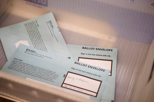 Mail-in ballots lay in a sorting bin at the Department of Elections New Castle County Office Wednesday, Oct. 14, 2020.