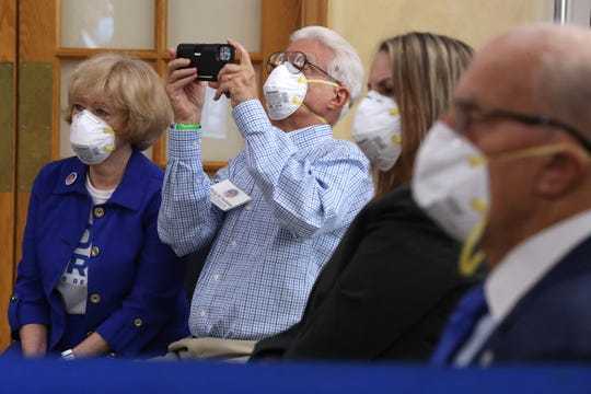 Philip Fortman (2nd-L) makes a photograph as he and his wife Karen Fortman listen to Democratic presidential nominee Joe Biden deliver remarks about his 'vision for older Americans' at Southwest Focal Point Community Center October 13, 2020 in Pembroke Pines, Florida.