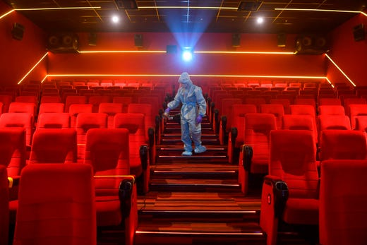 A worker sanitizes a theatre hall ahead of the scheduled reopening of cinemas as theCOVID-19 coronavirus imposed lockdown eases further in Mumbai on Oct. 13, 2020.