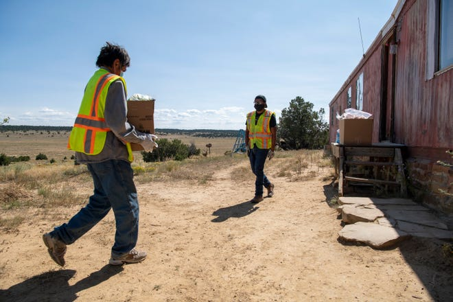David Martine (left) and Vernard Martinez (right) deliver supplies to the home of Gilbert Martinez on the Ramah Navajo Indian Reservation in New Mexico.