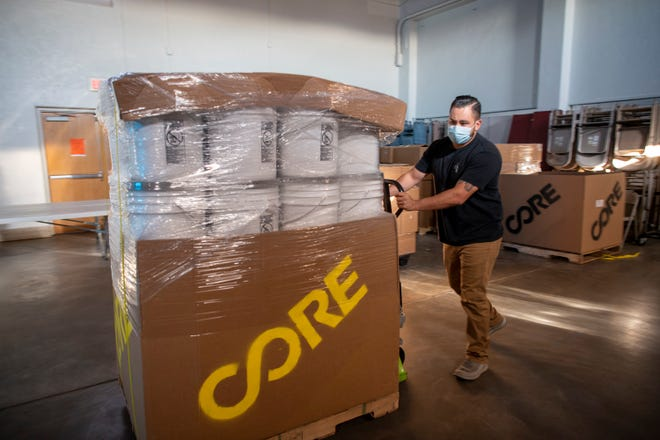 Christian Vasquez, deputy director of Strengthening Nations, pushes a pallet of sanitary kits through the First United Methodist Church as part of an effort by McKinley Mutual Aid in Gallup, N.M.