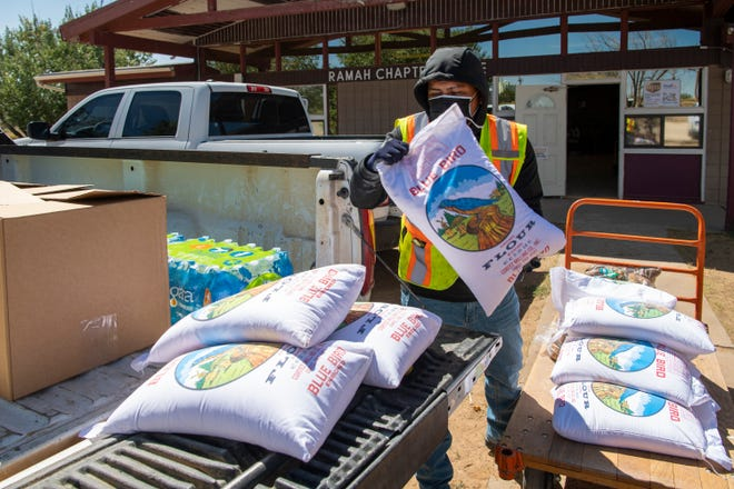 Jimmie Begay loads bags of flour onto a truck for delivery to at-risk residents on the Ramah Navajo Reservation in New Mexico. The Ramah distribution team receives support from nonprofits including Navajo and Hopi Families COVID-19 Relief Fund and McKinley Mutual Aid.