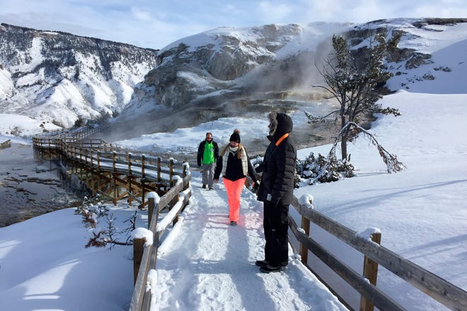 In this Jan. 20, 2017, file photo, James Kristy and Ginger Lee of Palm Beach County, Fla., walk the boardwalk at Mammoth Hot Springs in Yellowstone National Park, Mont. Officials say there will be no guest lodging at Yellowstone National Park's largest lodge for the winter due to the coronavirus pandemic.