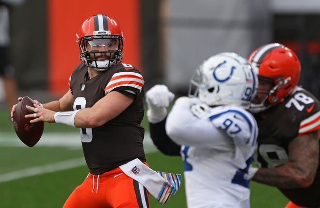 Browns quarterback Baker Mayfield looks downfield as Indianapolis Colts defensive end Al-Quadin Muhammad closes in Sunday in Cleveland.
