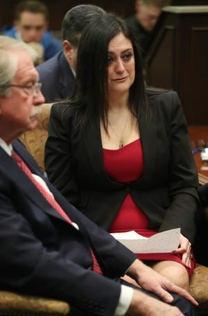 Attorney Lawrence Whitney listens as his client Laura Bucy, a former teacher at Twinsburg High School, reads a statement before her sentencing in Summit County Common Pleas Court in January.