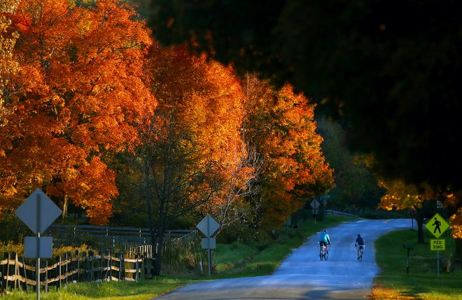 Cyclists ride side-by-side down Oak Hill Road on Tuesday in Bath Township.