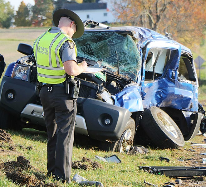 A state trooper from the Ashland Post of the State Highway Patrol investigates a crash Wednesday evening at State Route 603 and Ashland County Road 1475.  An Ashland woman was seriously hurt in the crash.