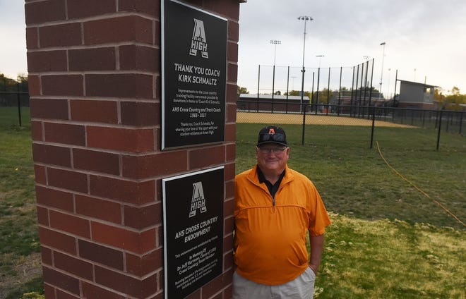 Former Ames High girls' cross country coach Kirk Schmaltz poses in front dedication plaque during the dedication ceremony of coach Schmaltz and Dr. Jeff Hartman at the Ames High baseball and softball complex Wednesday in Ames.