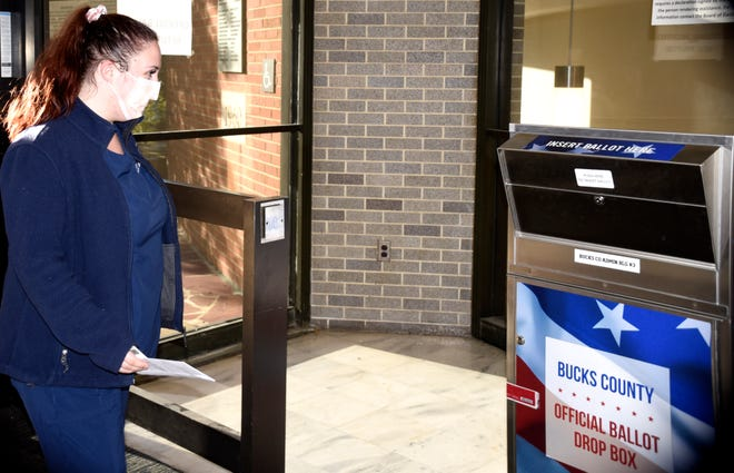 Alex Berkhimer walks her ballot over to Bucks County's official ballot drop box Thursday morning. Dozens of voters trickled into the county's administration building in Doylestown Borough to vote.