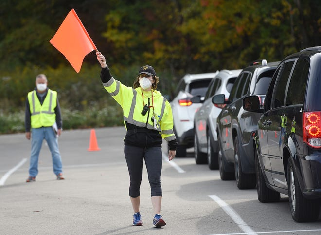 Rachel Zaydak, distributions coordinator with the Greater Pittsburgh Community Food Bank, directs a line of cars at a food drive Oct. 10 at Pathway Church in Chippewa Township. More than 200 families were served.