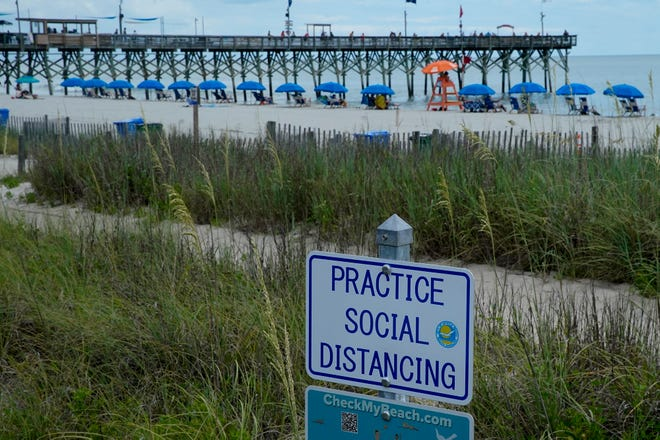 Beach umbrellas are separated past a sign urging social distancing on the sand July 9 in Myrtle Beach.