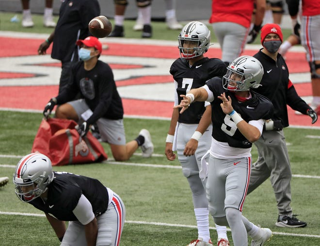 Jack Miller throws during a drill in Ohio Stadium on Oct. 3. He and C.J. Stroud, watching him throw, enrolled early at Ohio State but got limited exposure to the offense because of the coronavirus pandemic.