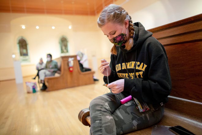 """Kylee May, a junior at Ohio Dominican University majoring in graphic design, sews a """"Vote"""" pin inside the Wehrle Gallery on campus."""