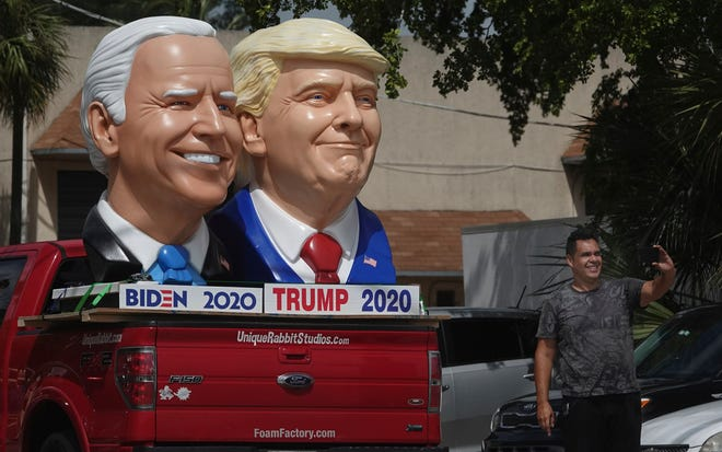 A passerby stops to take a selfie with foam sculpture depictions of President Donald Trump and Democratic presidential candidate Joe Biden along the Dixie Highway in Fort Lauderdale, Florida, last month.
