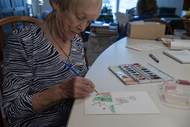 Bonnie Bowen paints a rendition of her eight-year-old granddaughter, Angel Bowen, in her Upper Arlington, Ohio, home while her daughter, Betsy Hampton, chooses which of her motherís paintings will be part of the calendars they are creating on Oct. 14, 2020.