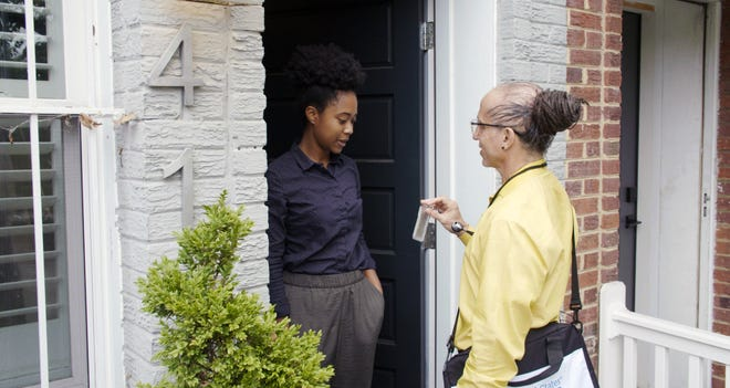 A census worker shows her badge to a resident during in-person data collection.