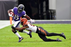 Baltimore Ravens wide receiver Marquise Brown (15) is tackled by Cincinnati Bengals linebacker Akeem Davis-Gaither (59) during the first half of an NFL football game on Sunday in Baltimore. The Ravens defeated the Bengals 27-3. [The Associated Press]