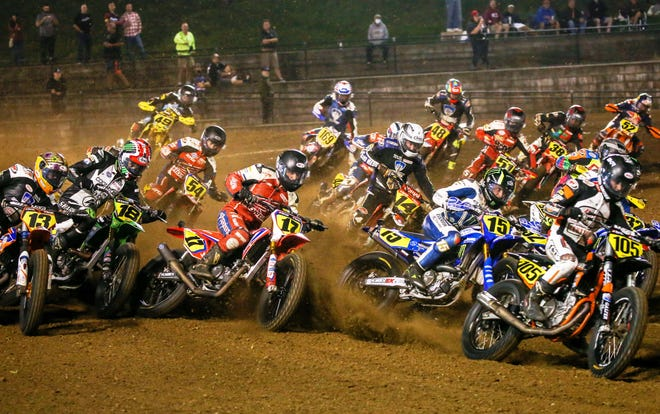 A group of American Flat Track riders attack the half mile course at Volusia Speedway Park in July.