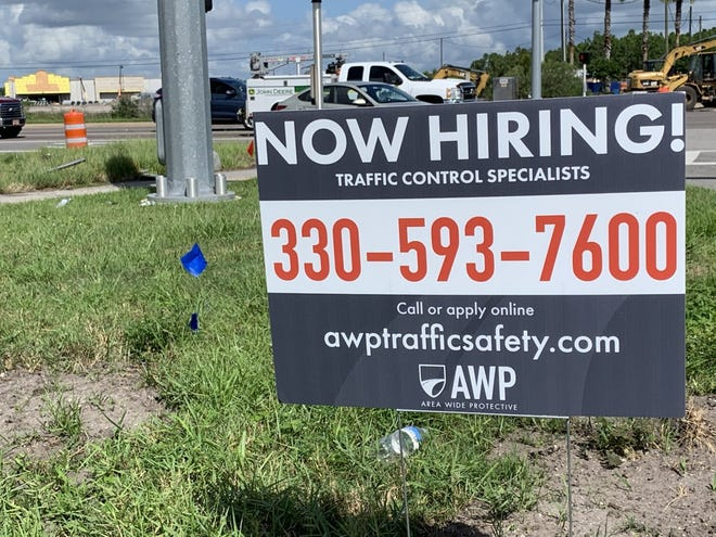 A hiring sign can be seen along LPGA Boulevard, just east of Interstate 95, in Daytona Beach on Aug. 27, 2020. The future Buc-ee's gas station can be seen under construction in the distance. The chain has already begun advertising to fill management positions at the 120-pump gas station that will be the largest in Florida when it opens in spring 2021. It will include a 53,000-square-foot travel convenience center.