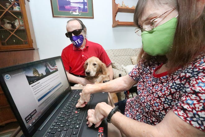 Doug Hall, who is blind, cast his vote for the upcoming election through OmniBallot, a platform that facilitates online voting. He sits in his Daytona Beach home with his dog Watson, as his wife Nancy Burgess-Hall, who has rheumatoid arthritis, visits the OmniBallot website, Thursday October 15, 2020.