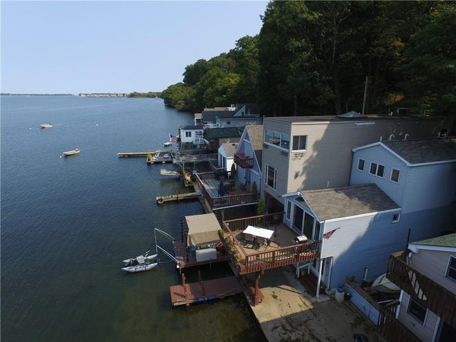 The cottage at 16 Ferncliff Beach, shown in the foreground with the American flag on the deck, will be sold at auction on Oct. 24 with a starting bid at $400,000.