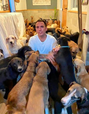 In this Oct. 7 photo, Ricardo Pimentel plays with dogs that he sheltered at his home in Leona Vicario, Mexico, during Hurricane Delta.