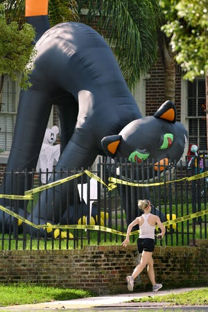A giant inflatable black cat keeps a watchful eye on passers-by from a yard at Willow Branch Avenue and Park Street on a recent morning in Jacksonville. The cat is one of many Halloween-themed inflatables filling most of the lawn of the residence. COVID-19 has altered a lot of traditional Halloween plans this holiday.