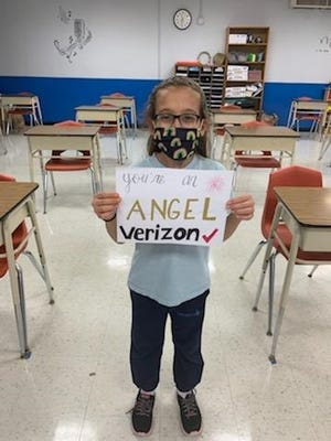 A student attending St. Ephrem School holds up a card to thank Verizon for funding scholarships through the Bridge Educational Foundation.
