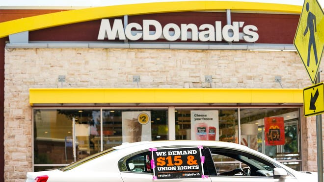 A car drives through the drive-thru of a McDonalds on Busch Boulevard in Tampa while participating in a caravan to advocate for increasing the minimum wage to $15 by voting yes on Amendment 2.